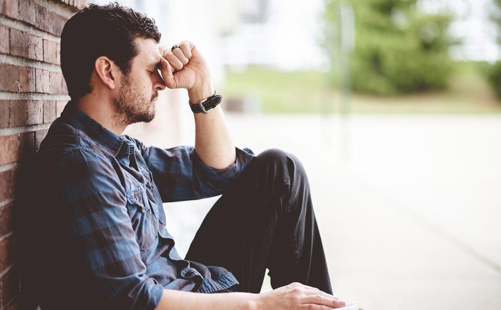 Una persona deprimida solitaria sentada cerca de una pared de ladrillos