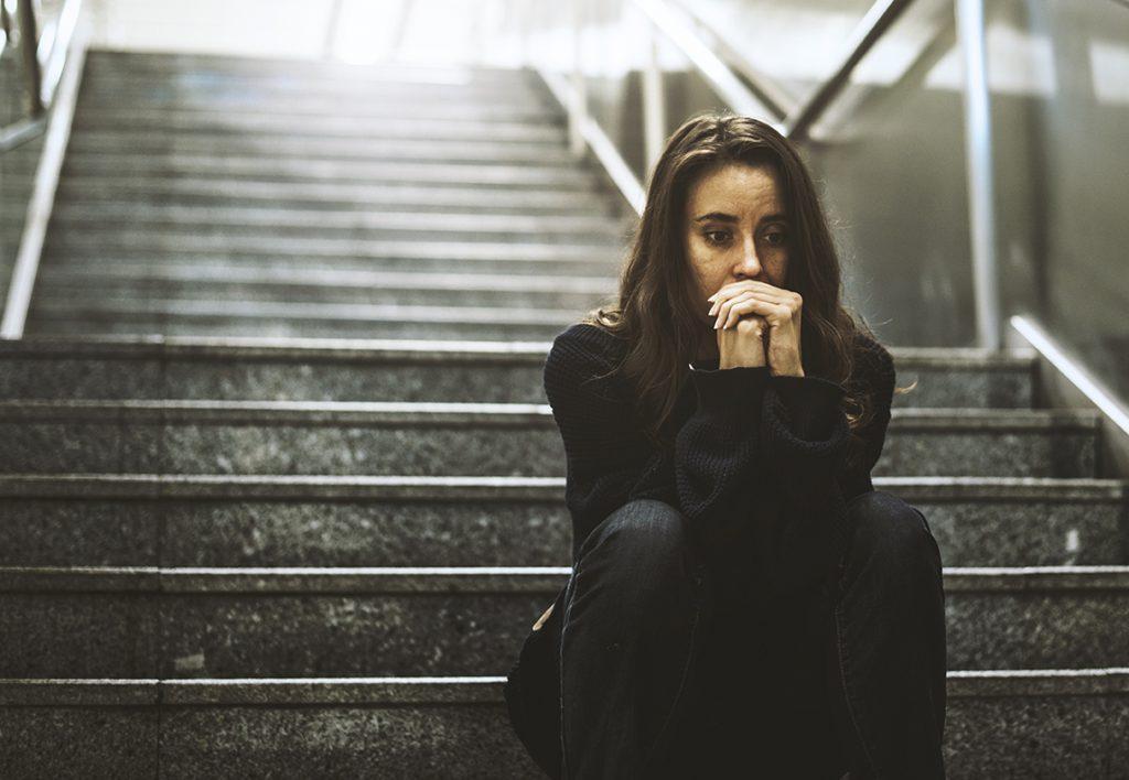 Mujer sentada mirada preocupada en la escalera
