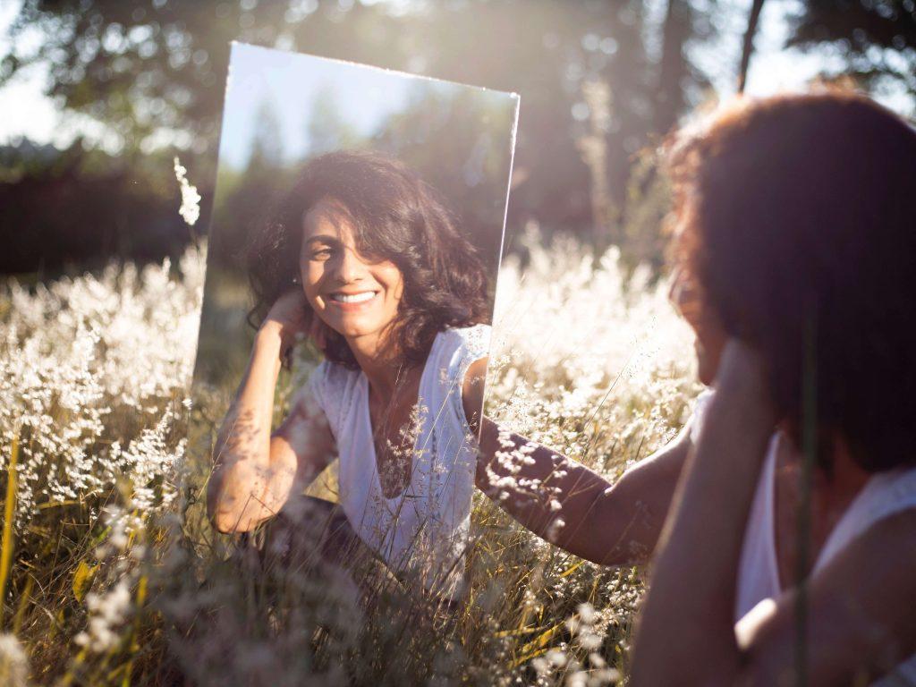 Mujer en la pradera feliz por superar su relación pasada mientras observa un reflejo de ella en la montaña