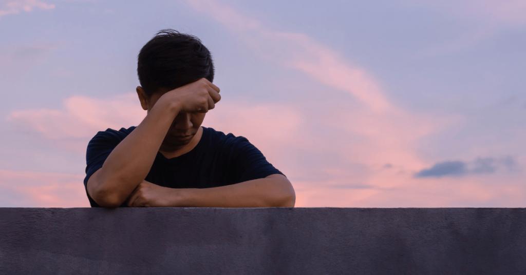 una persona reposando su brazo sobre una barda de concreto triste por una perdida